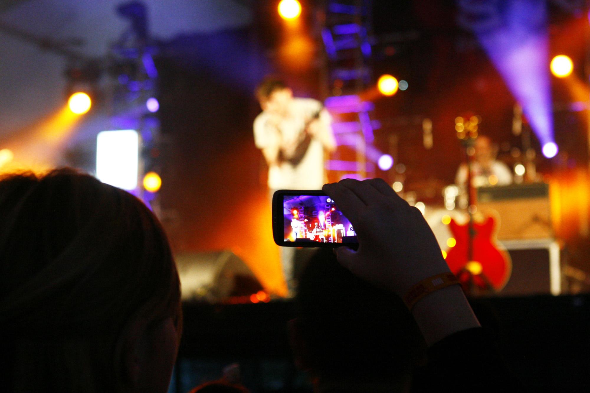 Un fan saca unha foto durante o concerto de Ellos