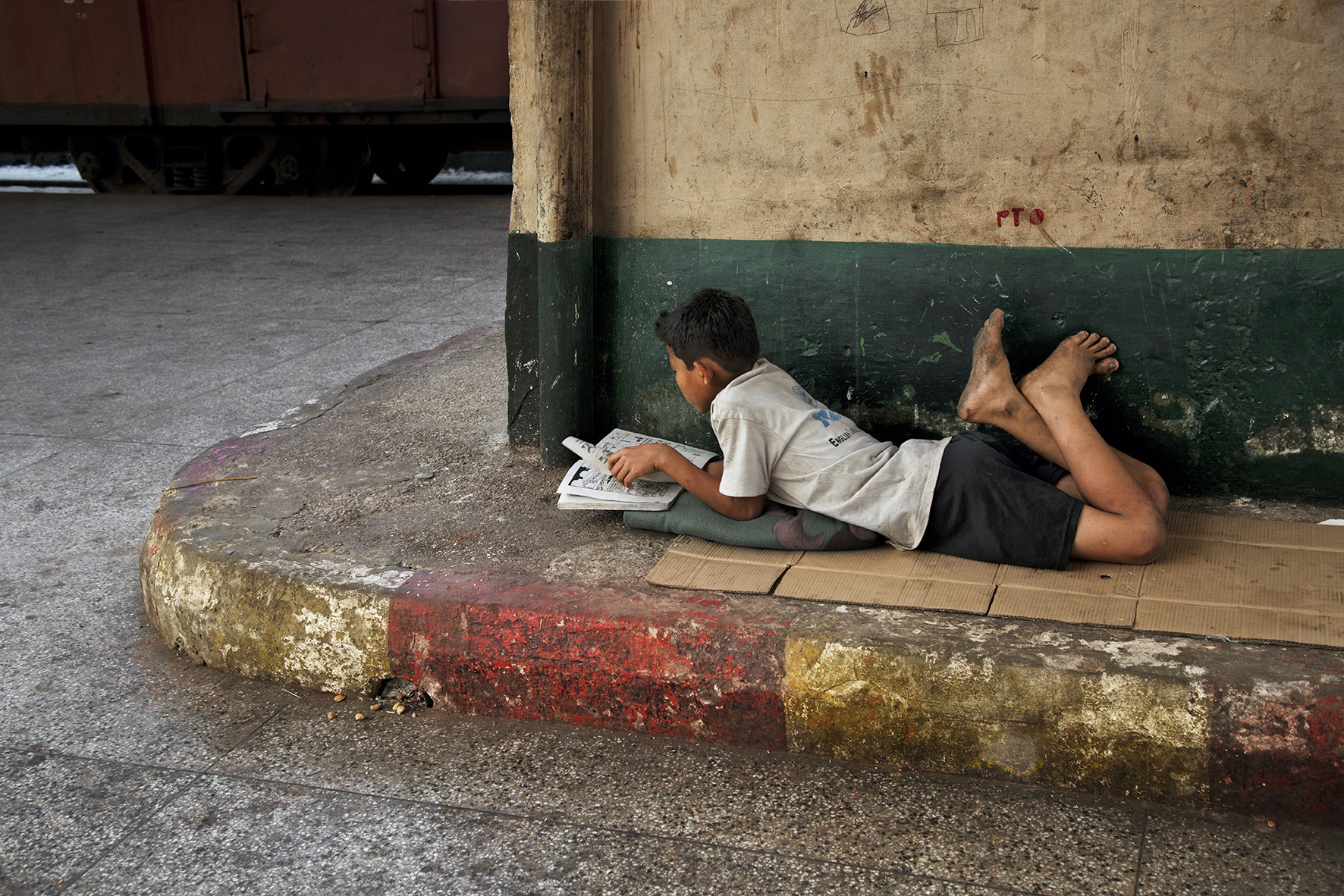 DSC_4524, Burma/Mynamar, 01/2014, BURMA-10711. A boy lies on the sidewalk and reads.  Retouched_Sonny Fabbri 05/21/2014