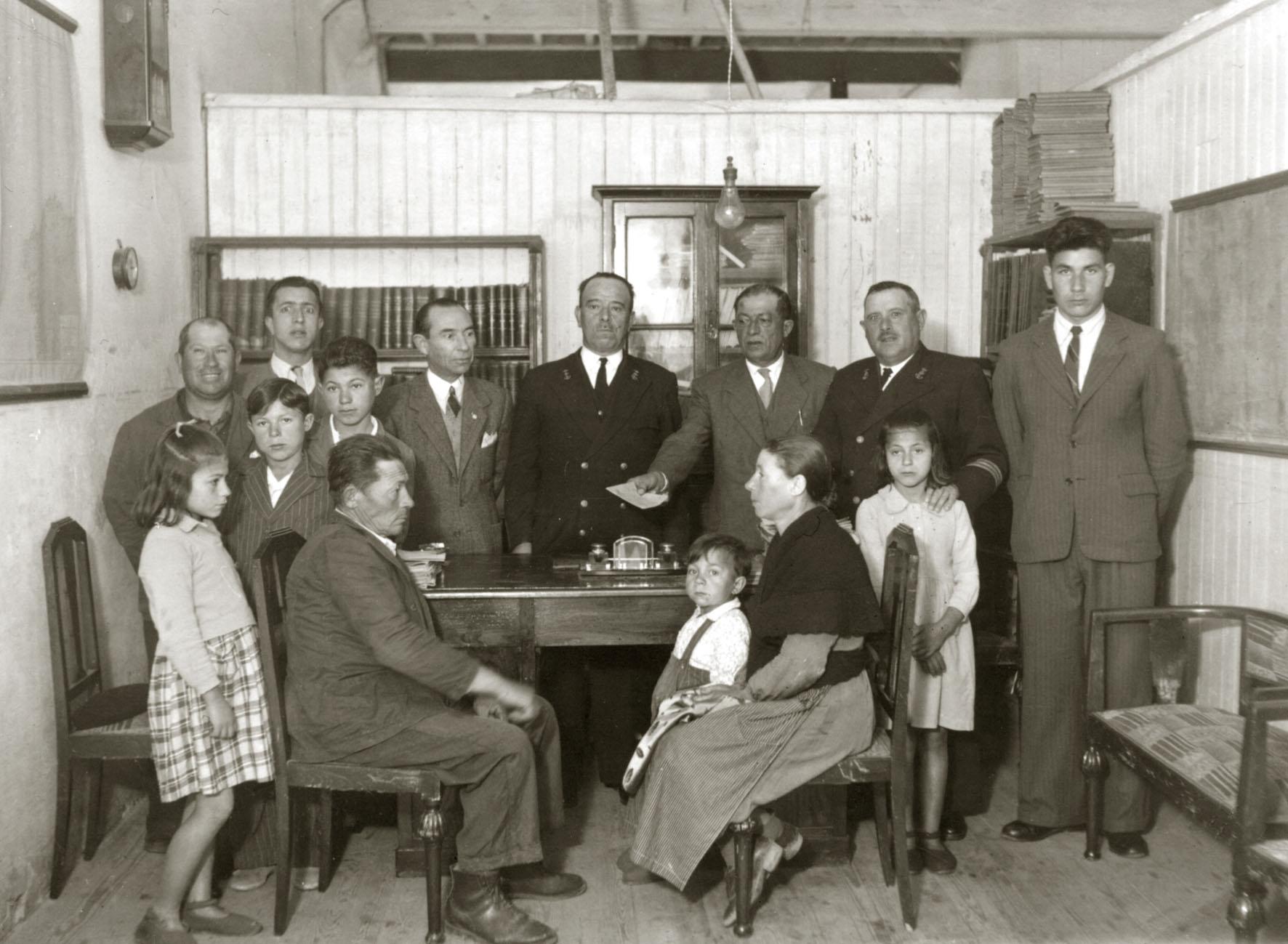A familia dun mariñeiro desparecido no mar recibindo unha paga, 1950